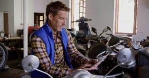 Mannelijke werktuigkundige die digitale tablet in de garage 4k gebruiken van de motorreparatie stock videobeelden