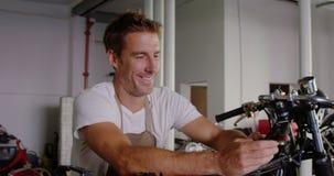 Mannelijke werktuigkundige die mobiele telefoon in de garage 4k met behulp van van de motorreparatie stock footage