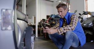 Mannelijke werktuigkundige die mobiele telefoon in de garage 4k met behulp van van de motorreparatie stock video