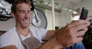 Mannelijke werktuigkundige die mobiele telefoon in de garage 4k met behulp van van de motorreparatie stock videobeelden