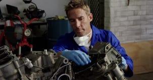 Mannelijke werktuigkundige die motordelen in reparatiegarage 4k herstellen stock video