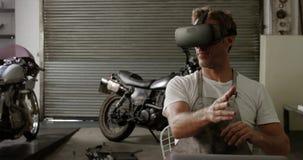 Mannelijke werktuigkundige die virtuele werkelijkheidshoofdtelefoon in de garage 4k met behulp van van de motorreparatie stock videobeelden
