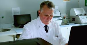 Mannelijke wetenschapper die aan bureau 4k werken stock videobeelden