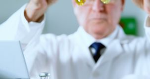Mannelijke wetenschapper die medische flesjes plaatsen op een rek 4k stock videobeelden
