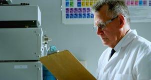 Mannelijke wetenschapper die op klembord 4k schrijven stock footage