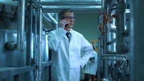 Mannelijke wetenschapper die over zijn telefoon in laboratorium rapporteren stock videobeelden