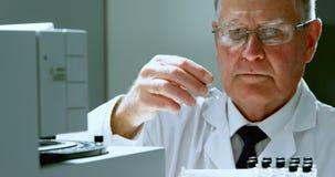 Mannelijke wetenschapper die reageerbuis plaatsen op een machine 4k stock video
