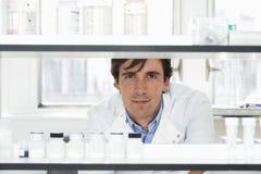 Mannelijke Wetenschapper Looking Through Shelves stock afbeelding