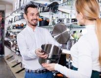 Mannelijke winkel hulp helpende klant om steelpan te kiezen royalty-vrije stock afbeelding