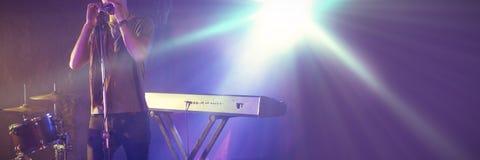 Mannelijke zanger die op verlicht stadium in nachtclub presteren royalty-vrije stock foto