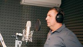 Mannelijke zanger in hoofdtelefoons die lied zingen in de microfoon bij correcte studio Amusementsbedrijfconcept Volwassen mens d stock video