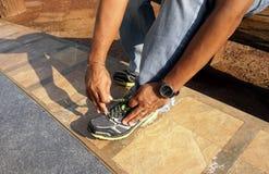 Mannelijke zittende en bindende schoenveters Royalty-vrije Stock Afbeeldingen