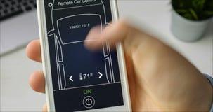 Mannen ändrar avlägset temperatur i hans bilbilfjärrkontroll genom att använda den uppdiktade manöverenheten för smartphoneapplik arkivfilmer