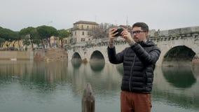 Mannen är att fotografera som är i stadens centrum vid smartphonen arkivfilmer
