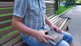 Mannen är den hållande heliga bibeln i hans handsammanträde på en bänk i en parkera i sommaren på en solig dag stock video