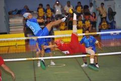 Mannen är hög blockera bollen på det netto i lek av sparkvolleyboll, sepaktakraw Royaltyfria Foton