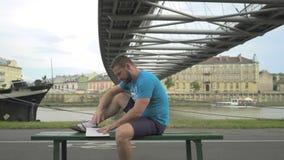 Mannen är läseboken som sitter på bänk mot floden lager videofilmer