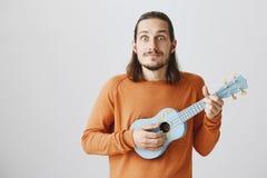 Mannen är lycklig lär slutligen det nya ackordet Positiv stilig grabb med roligt uttryck i orange ukulele för tröjainnehavblått arkivbilder