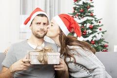 Mannen är misstrogen om julgåvan Arkivbild