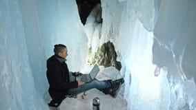 Mannen är sitter på internet i bärbar dator i en isgrotta Runt om den mystiska härliga isgrottan Användaren meddelar in arkivfilmer