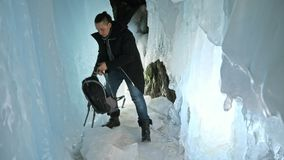 Mannen är sitter på internet i bärbar dator i en isgrotta Runt om den mystiska härliga isgrottan Användaren meddelar in stock video