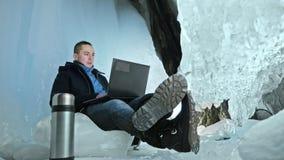 Mannen är sitter på internet i bärbar dator i en isgrotta Runt om den mystiska härliga isgrottan Användaren meddelar in lager videofilmer