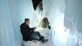 Mannen är sitter på internet i minnestavla i en isgrotta Runt om den mystiska härliga isgrottan Användaren meddelar in arkivfilmer