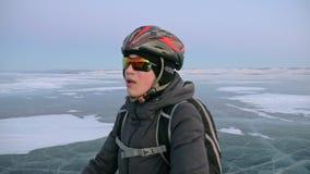 Mannen är ställningen per cykeln på is Han ser den härliga solnedgången Cyklisten är iklädd en grå färg klår upp, vandrar ner stock video