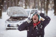 Mannen är under spänning därför att hans brutna ner bil Vinterlopp a fotografering för bildbyråer