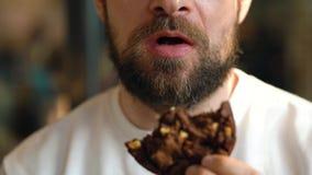 Mannen äter a-choklade kakor i ett kafé stock video