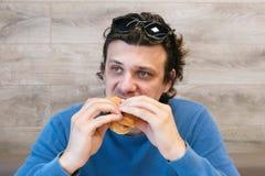 Mannen äter en hotdog i kafé arkivbild