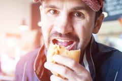 Mannen äter en paj i en vägrenmatställe royaltyfri fotografi