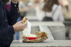 Mannen äter en snabbmat på gatan arkivfoto