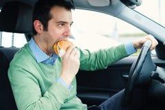 Mannen äter farligt skräpmat och den kalla drinken, medan köra hans bil royaltyfria bilder