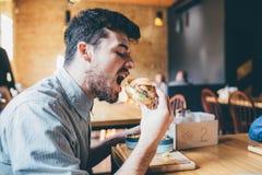 Mannen äter i en restaurang och tycker om läcker mat Royaltyfria Bilder
