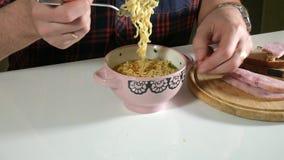 Mannen äter kinesiska ögonblickliga nudlar med en gaffel arkivfilmer