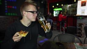 Mannen äter pizza Han rymmer ett stycke av pizza i hans händer och äter med en aptit lager videofilmer
