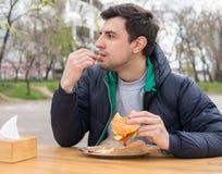 Mannen äter pommes frites i en mellanmålstång royaltyfria bilder