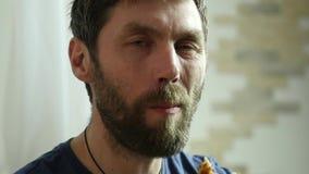 Mannen äter snabbmat, fega klumpar och vingar med en mousserande drink mycket skräpmat långsam rörelse stock video