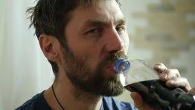Mannen äter snabbmat, fega klumpar och vingar med en mousserande drink mycket skräpmat långsam rörelse arkivfilmer