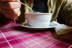 Mannen äter soppa på tabellen royaltyfri fotografi