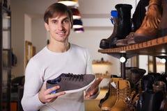 Mannen önskar att köpa skorna arkivbilder