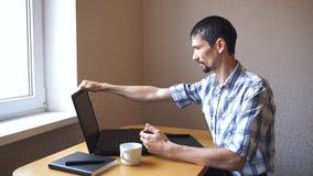 Mannen öppnar bärbar datorsammanträde på tabellen lager videofilmer