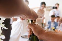 Mannen öppnar en flaska av champagneslutuo royaltyfri foto