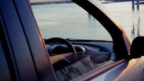 Mannen öppnar ett fönster i bilen och beundrar den härliga solnedgången på floden på bron som sitter i parkeringen stock video