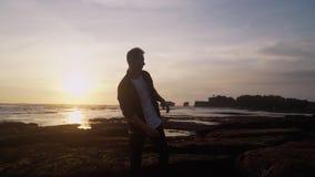 Mannen öppnar hans armar som är breda mot härlig guld- solnedgång på stranden, uttrycker avkänning av frihet, happines lager videofilmer