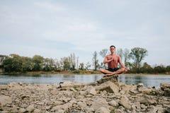 Mannen öva yoga på flodbanken Royaltyfri Foto