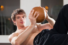 Mannen övar med medicinbollen i idrottshall Royaltyfri Foto