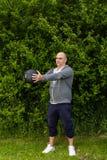 Mannen övar utomhus med en 3 kg medicinboll Arkivfoton