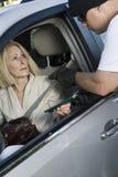 Mannen anfaller kvinnan med skjutvapnet till och med bilfönster Royaltyfri Foto